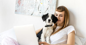 Person and puppy at computer